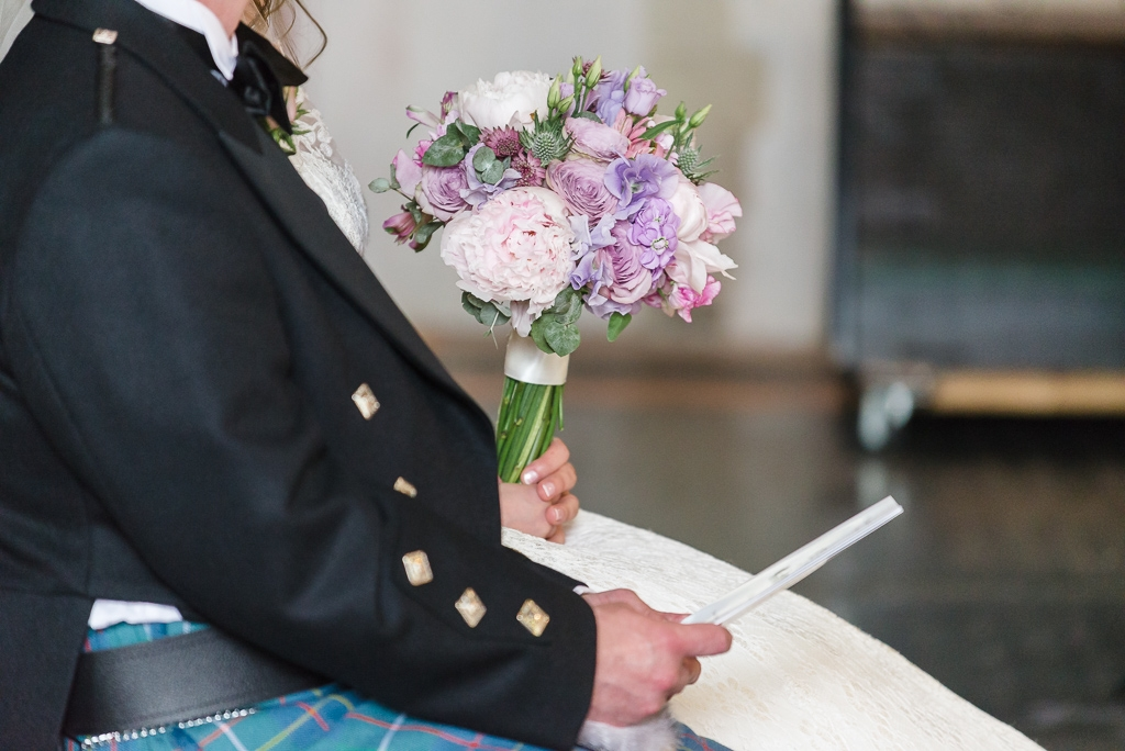 Detail photograph of groom's Scottish jacket and bride's bouquet at St Paulinus Church | Oakhouse Photography