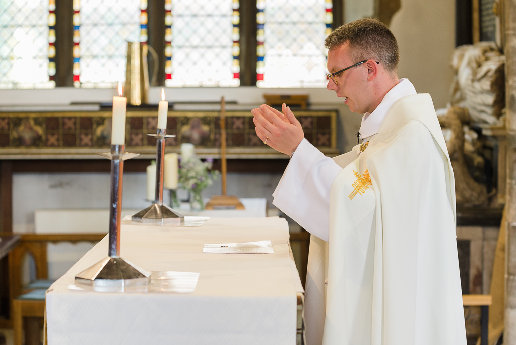 Priest blessing the wedding rings at St Paulinus Church Crayford wedding | Oakhouse Photography