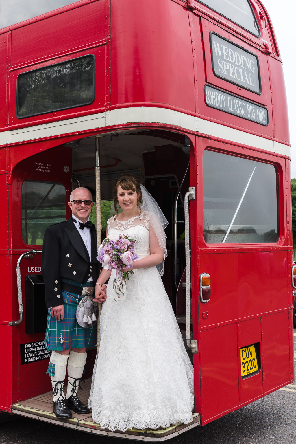 Bride and groom on steps of London bus transporting guests to Hall Place Bexley wedding reception venue | Oakhouse Photography