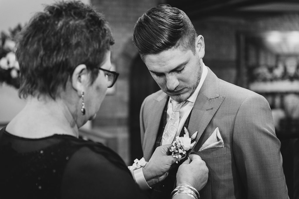 Groom's mother adding button hole to the groom's jacket before the wedding | Sidcup Wedding of Becky & Hugo | Oakhouse Photography