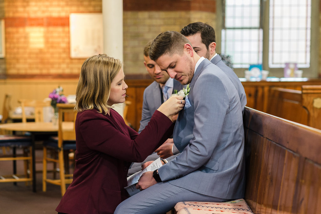 Groom's sister adjusting buttonhole | Sidcup Wedding of Becky & Hugo | Oakhouse Photography