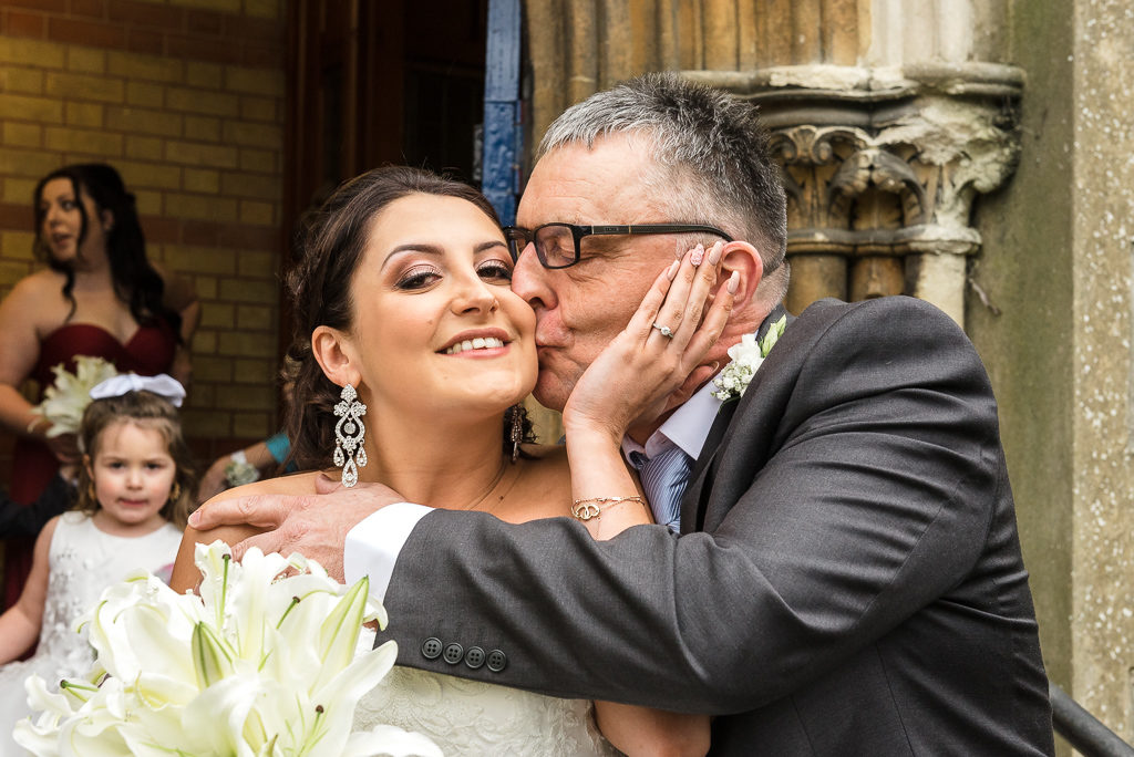 Fun shot of bride being kissed by her father before the ceremony | Sidcup Wedding of Becky & Hugo | Oakhouse Photography