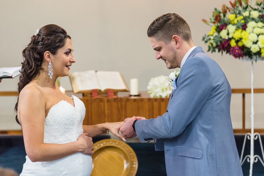 Groom placing ring on bride's hand | Sidcup Wedding of Becky & Hugo | Oakhouse Photography