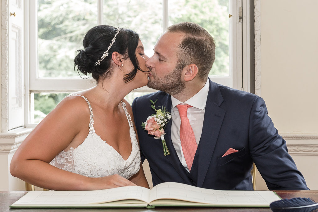 Bride and groom kiss after signing the register at Danson House Bexley wedding | Oakhouse Photography