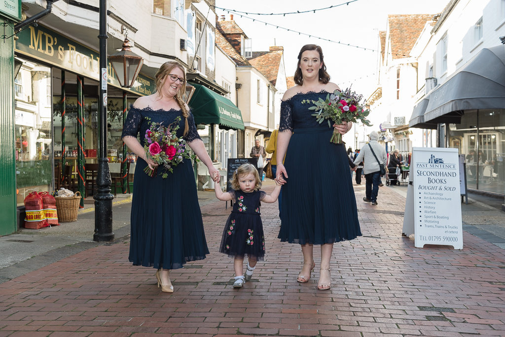 Bridesmaids and flower girl walking through Faversham town centre on the way to the wedding ceremony | Oakhouse Photography