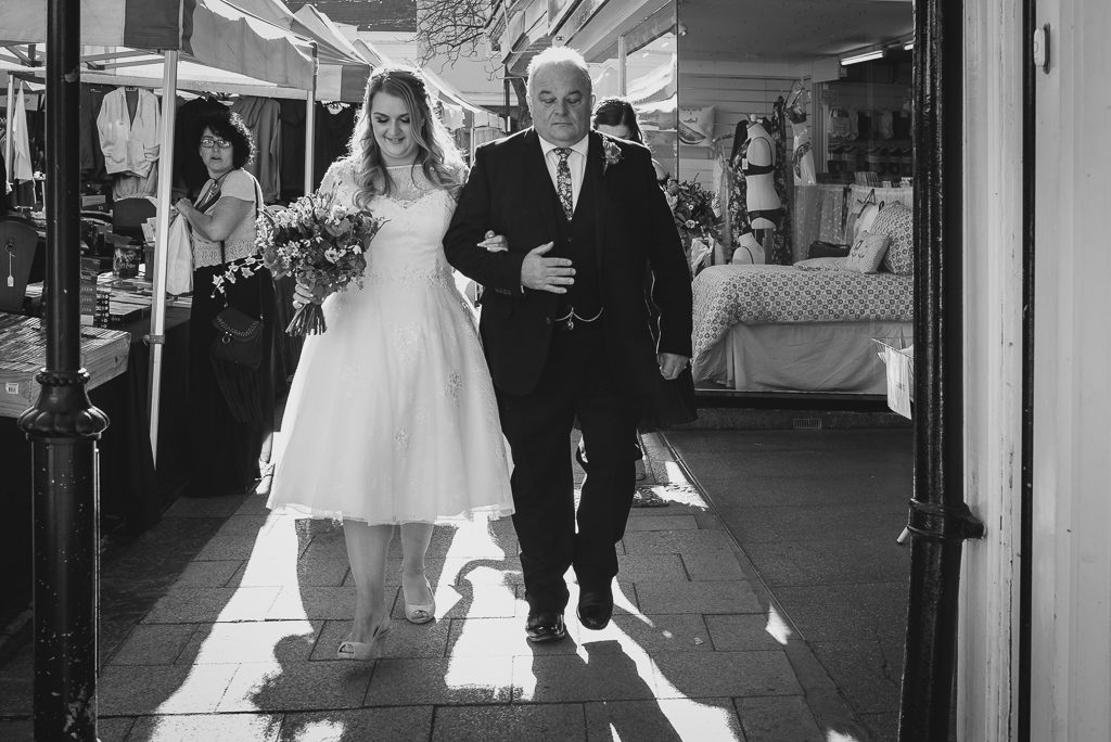 Bride and father walking through Faversham town centre on the way to the wedding ceremony | Oakhouse Photography